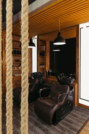 close-up view of ropes and empty leather chairs and sinks in modern barbershop