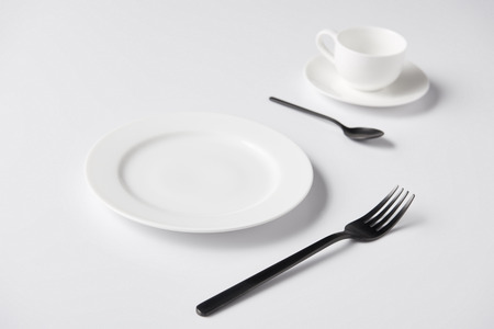 selective focus of plate, fork, spoon and cup on white table Stockfoto