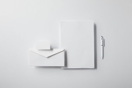 top view of arranged envelope with pen, blank paper and business card on white tabletop for mockup Stock Photo
