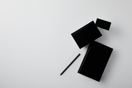 top view of black notebooks with business card and pencil on white surface for mockup
