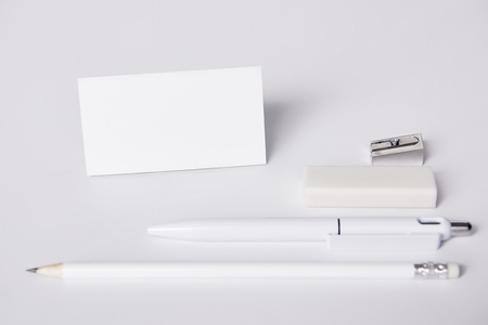close-up shot of business card and pen with pencil, eraser and sharpener arranged in row on white surface for mockup Stock Photo
