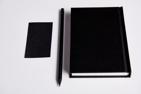 close-up shot of black notebook with pencil and blank business card on white surface for mockup 스톡 콘텐츠
