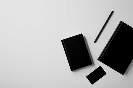 top view of black notebooks with business card and pencil on white tabletop for mockup