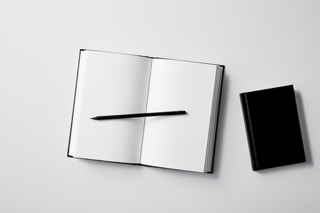 top view of black notebooks with pencil on white surface for mockup Imagens