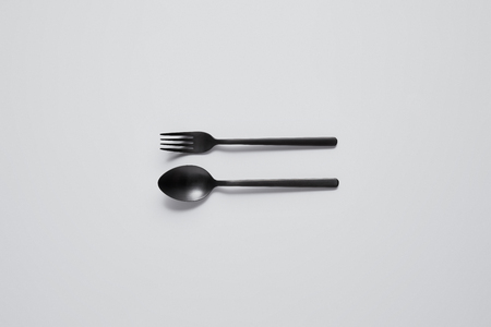 top view of black spoon and fork on white table, minimalistic concept 免版税图像