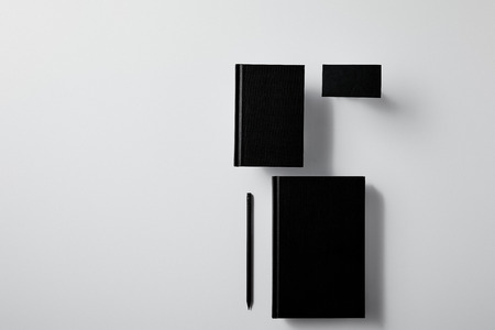 top view of arranged black notebooks with business card and pencil on white surface for mockup Banco de Imagens