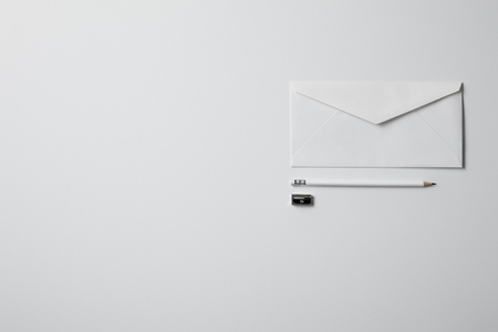 top view of envelope with pencil and sharpener on white surface for mockup