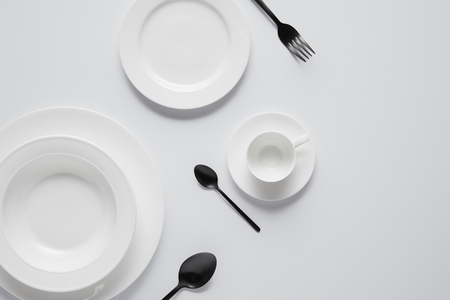 top view of various plates, cup, black spoons and fork on white table Stockfoto