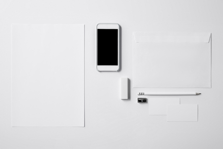 top view of smartphone with blank screen and office supplies on white tabletop for mockup