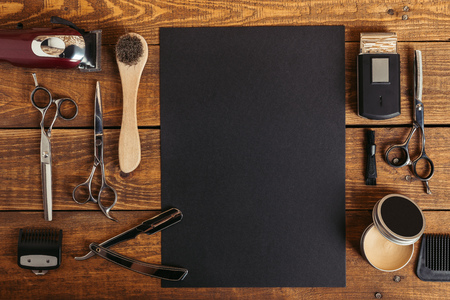 top view of professional barber tools and blank black card on wooden table Standard-Bild - 106503549