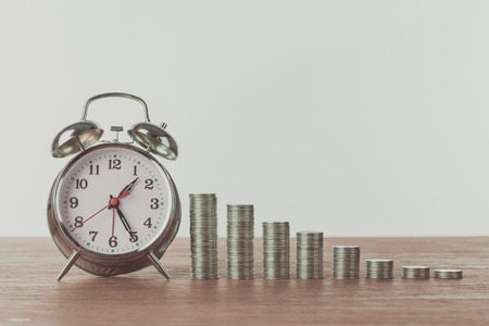 alarm clock and stacks of coins on wooden table, saving concept
