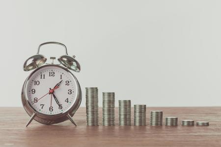 Wecker und Stapel von Münzen auf Holztisch, Sparkonzept