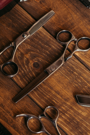 high angle view of professional scissors on wooden surface in barbershop