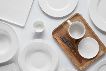 top view of cup, different plates, wooden tray, bowl and fork on white table Stockfoto