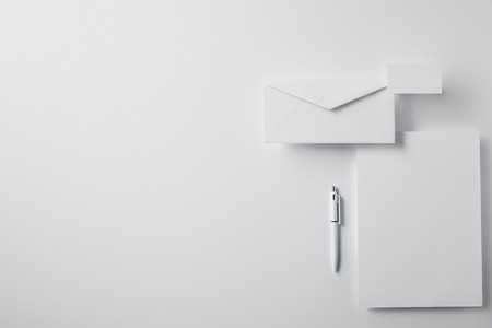 top view of layered envelope with pen, blank paper and business card on white surface for mockup Stock Photo