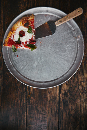 top view of slice of pizza with server on metal tray and wooden table Banque d'images - 106507050