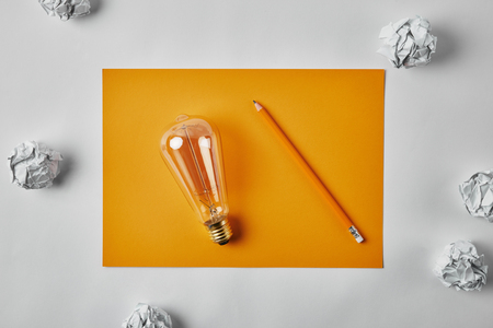 top view of incandescent lamp on blank yellow paper with pencil surrounded with crumpled papers on white surface Reklamní fotografie