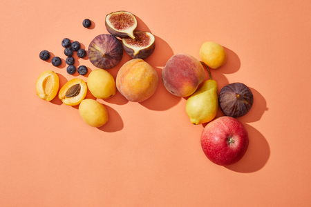 top view of fresh ripe sweet tasty fruits on red background