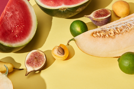 close-up view of sweet ripe watermelon, melon, limes, figs and apricots on yellow