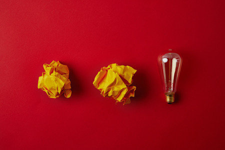 top view of crumpled yellow papers with incandescent lamp on red surface