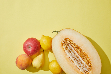 top view of halved melon, apple, peach, pear and lemons on yellow background