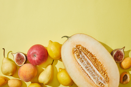 top view of halved melon and fresh ripe fruits on yellow background Stock Photo