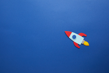 creative rocket on blue paper background