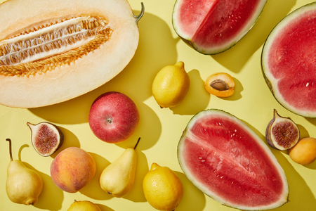 top view of fresh ripe sweet melon, watermelon, lemons, apple, fig, pear, peach and apricots on yellow