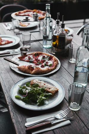 tasty italian dishes and drinks on wooden rustic table at restaurant Stock Photo
