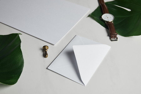 Blank envelope and watch on white marble background with green leaves
