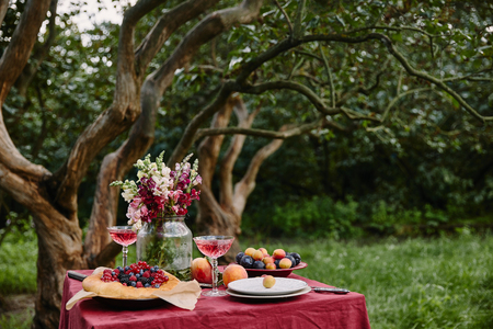 bouquet of flowers, wineglasses, fruits and pie on table in garden Reklamní fotografie