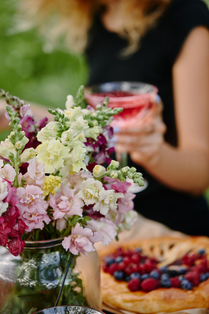 cropped image of woman holding glass of wine at table in garden with flowers on foreground