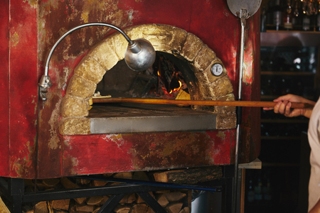 cropped shot of chef putting pizza into masonry oven at restaurant kitchen Stock Photo