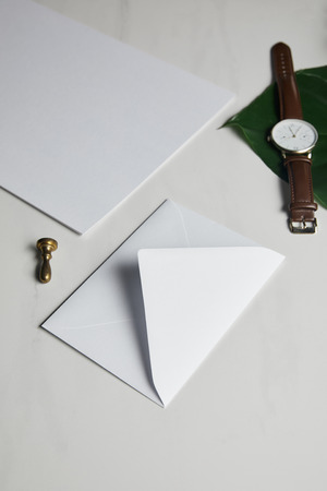 White envelope with brown watch on white marble background