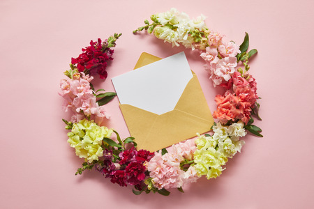 top view of beautiful tender flowers and blank card in envelope on pink
