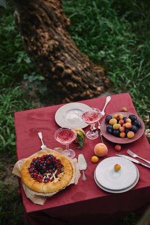 cooked berries pie and glasses of wine on table in garden