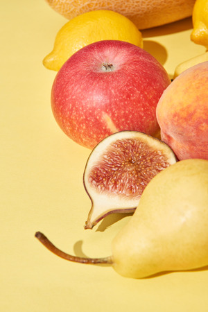 close-up view of fresh ripe pear, apple, peach, fig and lemons on yellow Stock Photo