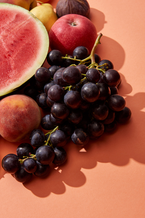 top view of fresh ripe sweet grapes, peach, apple and watermelon on red Stock Photo