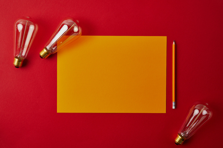 top view of blank yellow paper with pencil and incandescent lamps on red surface Banco de Imagens