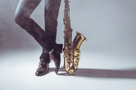 low section of professional musician standing with saxophone in smoke on grey Foto de archivo