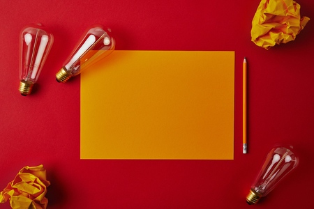 top view of yellow blank paper with crumpled papers and incandescent lamps on red surface Imagens - 106683663