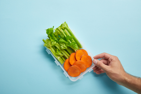 cropped shot of male hand and food container full of celery and carrot slices isolated on blue
