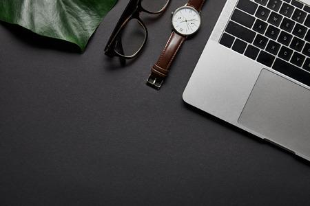 Glasses and watch by laptop on black background Zdjęcie Seryjne