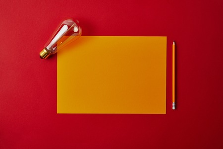top view of blank yellow paper with pencil and incandescent lamp on red surface