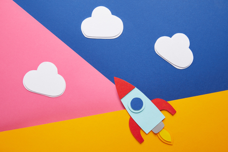 top view of clouds and colorful rocket on creative paper background Imagens