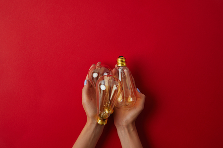 cropped shot of woman holding vintage incandescent lamps on red tabletop Archivio Fotografico
