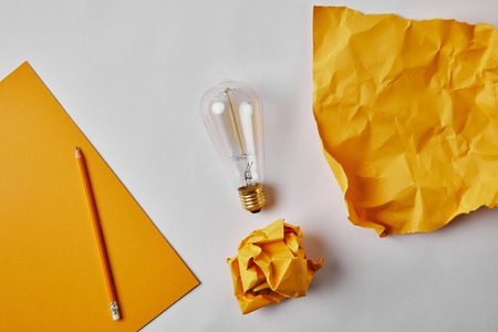 top view of yellow papers with vintage incandescent lamp and pencil on white surface Reklamní fotografie