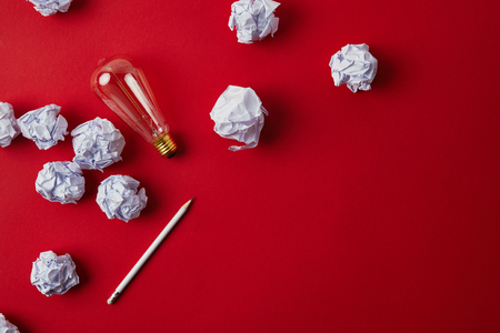 top view of crumpled papers with light bulb and pencil on red surface