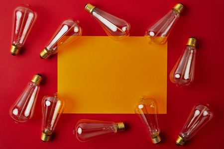 top view of vintage incandescent lamps on red surface with yellow blank paper