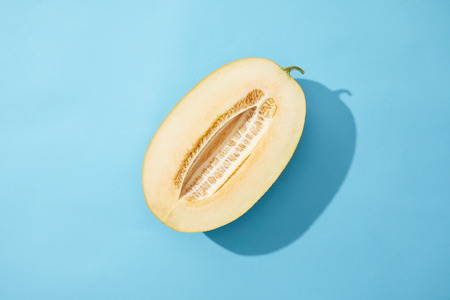 top view of half of fresh ripe sweet melon on blue background Archivio Fotografico